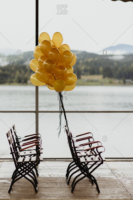 Gold balloons tied to a row of chairs