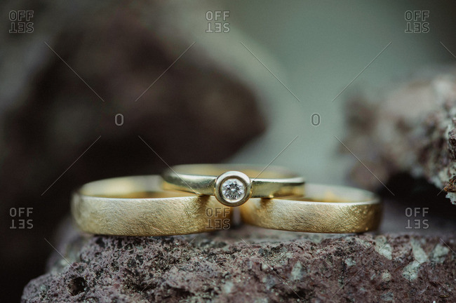 Close up of wedding rings sitting on a rock