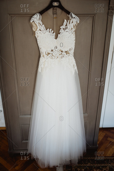 White wedding gown hanging from an armoire