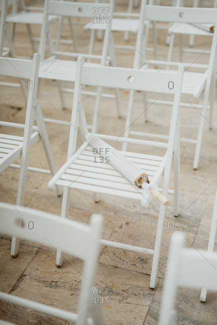 White wooden chair at a wedding ceremony with umbrella