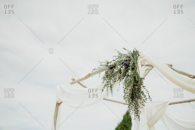 Wedding arbor with draped fabric and flowers