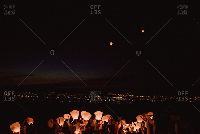 Wedding guests sending sky lanterns into the air at a reception