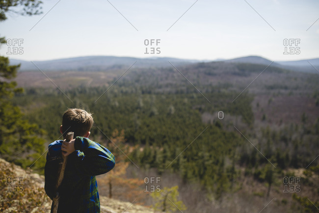 Boy holding a stick at a scenic lookout in the mountains