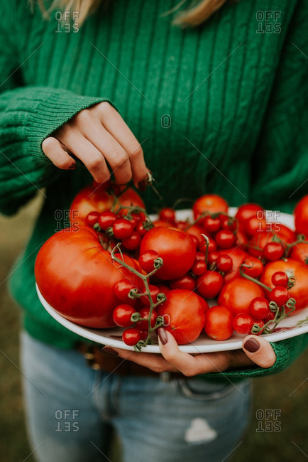 A woman holding a plate of vine-ripened tomatoes