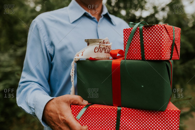 A man holding a stack of Christmas presents