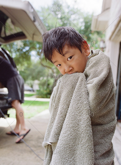 Boy standing in a driveway wrapped in a towel with wet hair