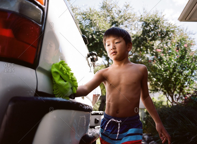 Boy washing the family car