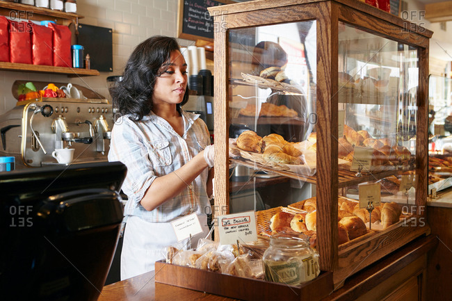 Female worker in bakery, putting fresh pasties into display cabinet
