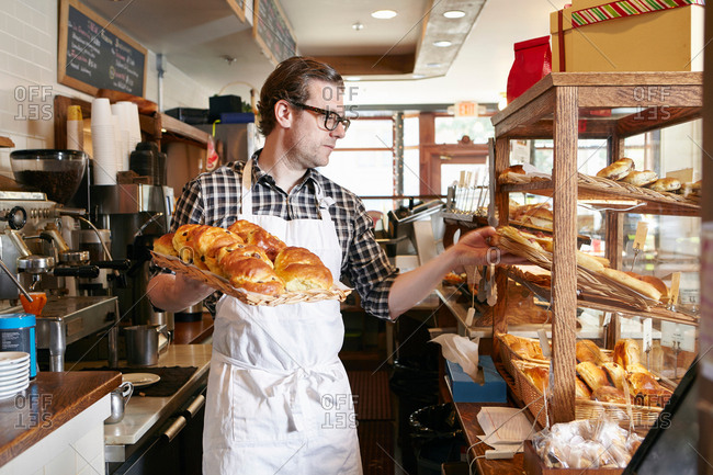 Male worker in bakery, putting fresh pastries into display cabinet