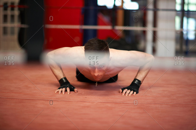 Boxer doing push-ups in boxing ring
