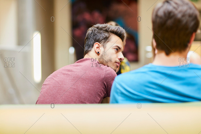 Rear view of male students in canteen at higher education college