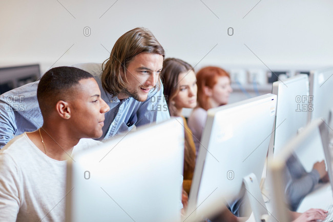 Male lecturer showing student using computer in higher education college computer room