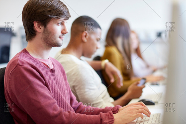 Students typing on computers in higher education college computer room
