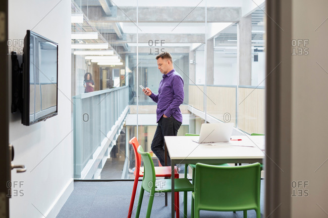 Male designer reading smartphone update in design studio