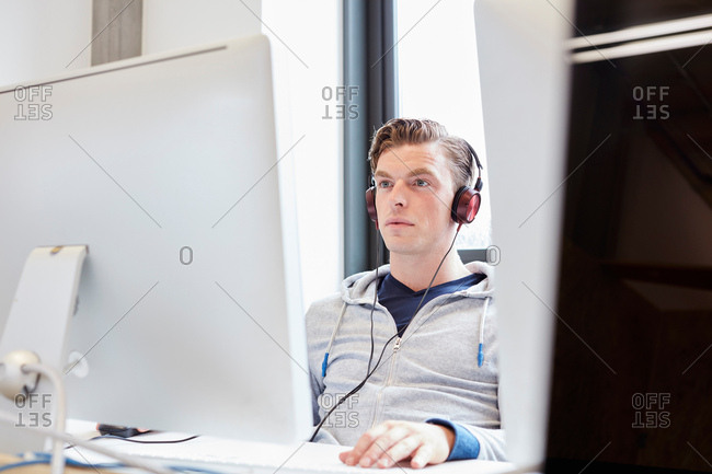 Young male computer aided designer working on computer in design studio