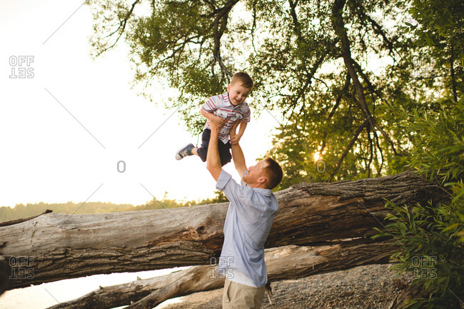 Father helping son jump from tree trunk at Lake Ontario, Oshawa, Canada