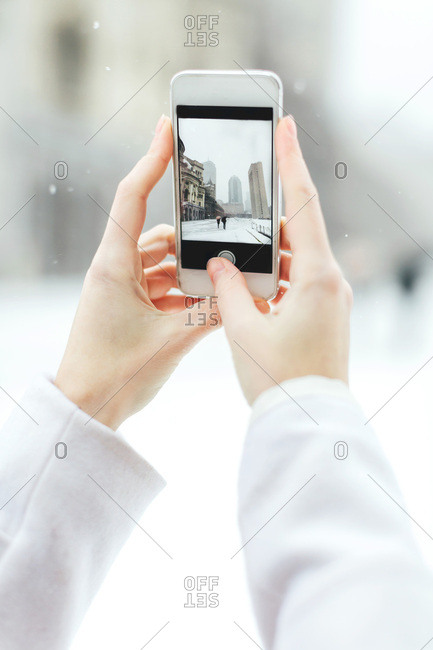 Young woman using smartphone to photograph the Christian Science Centre and Prudential building with snow, Boston, Massachusetts, USA