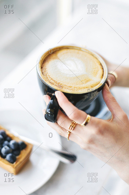 Woman's hands holding frothy coffee