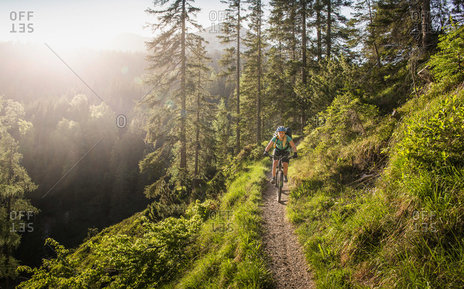 Woman mountain biking, Leermoos, Tyrol, Austria