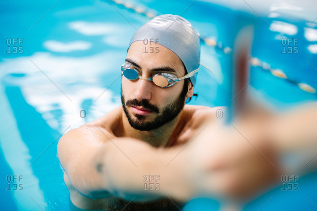 Man in swimming pool wearing swimming goggles