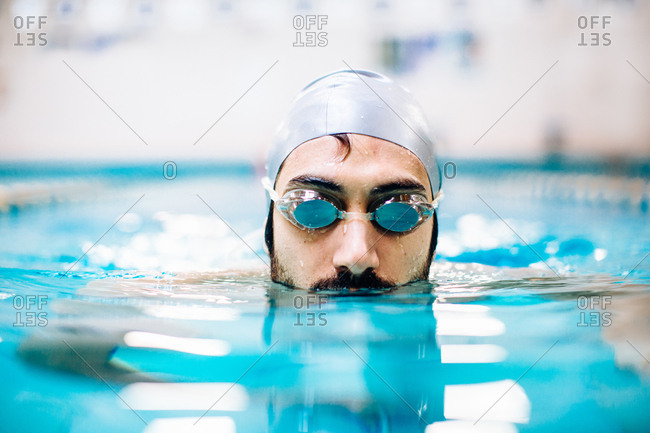 Man wearing swimming goggles and cap in swimming pool
