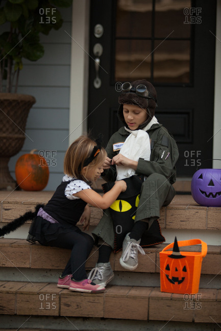 Boy and sister trick or treating in cat and pilot costume sitting on stairway looking in bags