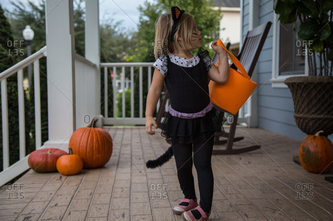 Girl trick or treating in cat costume looking over her shoulder on porch