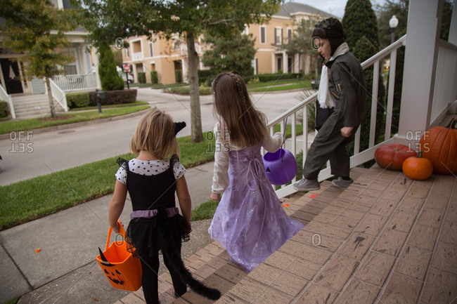 Boy and sisters trick or treating moving down porch stairway