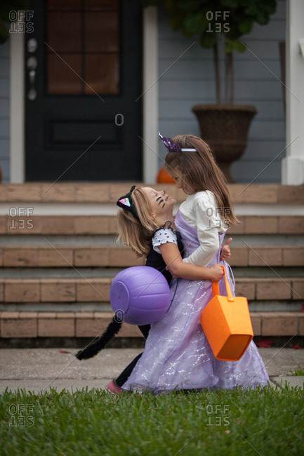 Two sisters trick or treating in cat and fairy costumes hugging at porch stairway