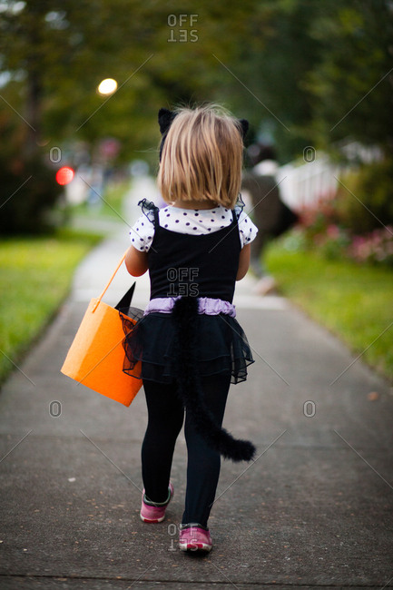 Rear view of girl trick or treating in cat costume walking along sidewalk