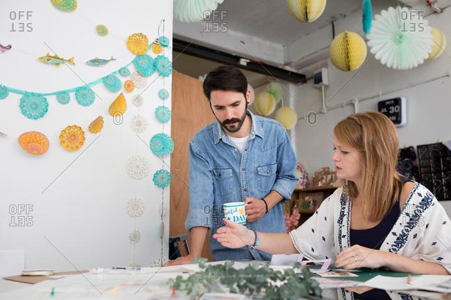 Female and male designer preparing mixed media design in printing press studio
