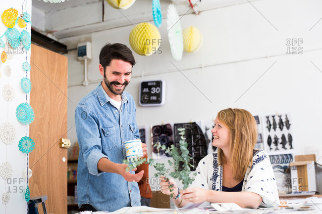 Female and male designer laughing at twig leaves in printing press studio