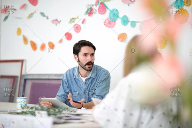 Female and male designer discussing mixed media design in printing press studio