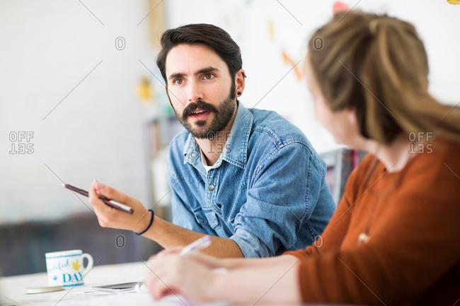 Female and male designer having team meeting in printing press studio