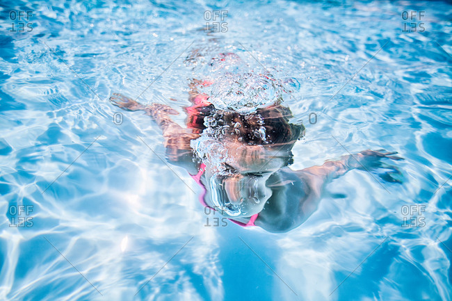 Girl swimming underwater in sunlit swimming pool