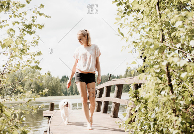 Woman with Coton de tulear dog strolling on lake pier, Orivesi, Finland