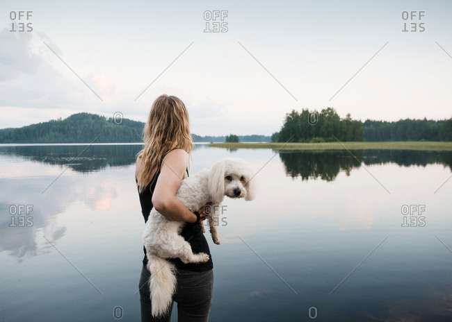 Woman carrying coton de tulear dog at lake, Orivesi, Finland