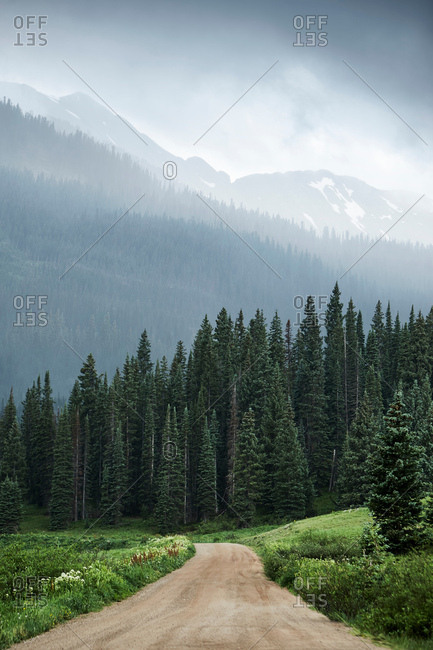 View of dirt track and low cloud over mountain forests, Crested Butte, Colorado, USA