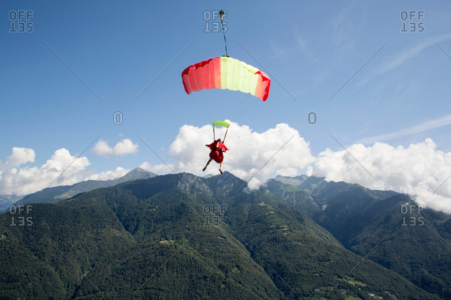 Skydiver under her parachute flying free in the blue sky, Locarno, Tessin, Switzerland