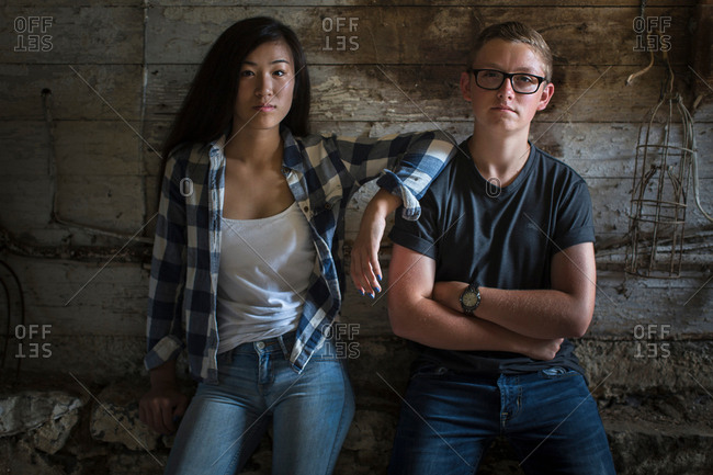 Portrait of sullen teenage couple leaning against dusty shed wall