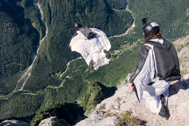 Wingsuit BASE jumper is flying down, filmed by another BASE jumper, Italian Alps, Alleghe, Belluno, Italy