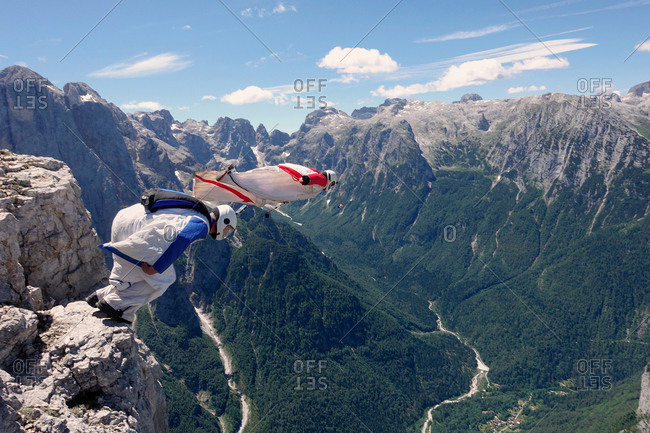 BASE jumping wingsuit pilots are jumping together from a cliff and down the valley, Italian Alps, Alleghe, Belluno, Italy