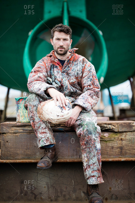 Portrait of male ship painter sitting in front of green ship hull
