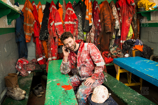 Male ship painter sitting in shed talking on smartphone