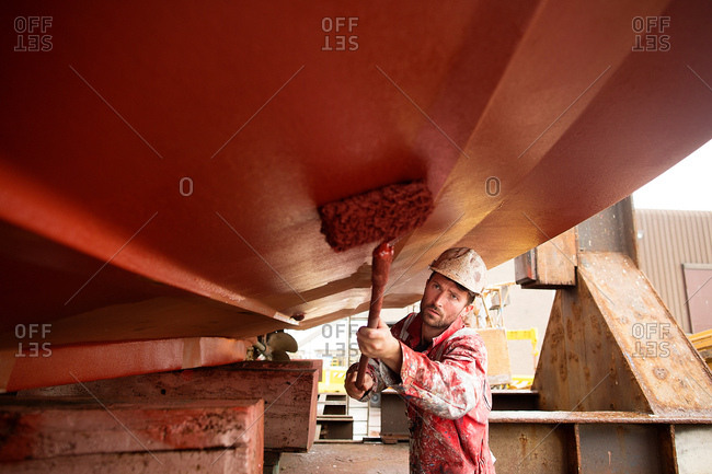 Male ship painter roller painting below ship hull in ship painters yard