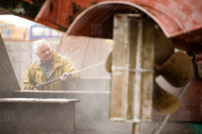 Senior male ship painter cleaning ship hull with pressure washer in ship painters yard