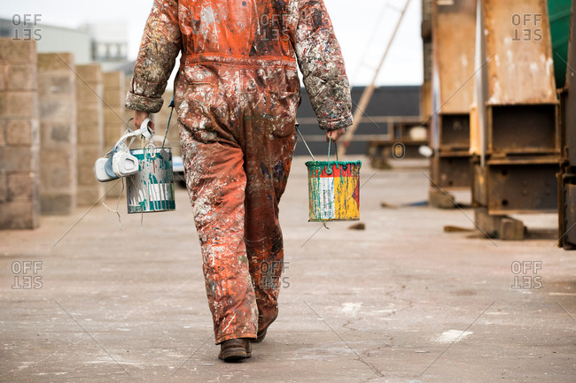 Neck down rear view of male ship painter carrying paint cans in ship painters yard