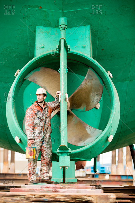 Male ship painter looking over shoulder in front of green ship hull in ship painters yard
