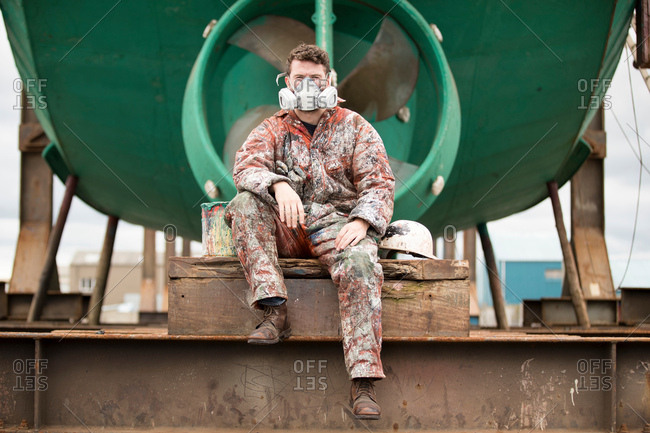Portrait of male ship painter wearing protective mask in front of green ship hull in ship painters yard