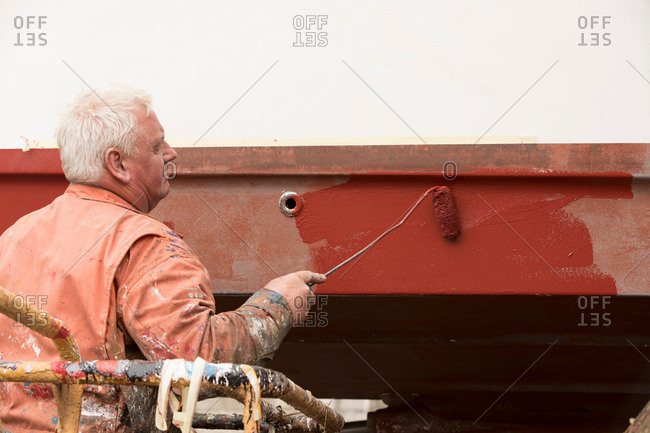 Senior male ship painter roller painting ship hull red in ship painters yard